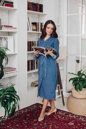 Elegant gorgeous brunette woman in denim dress and heels reading a magazine. Banco de Imagens