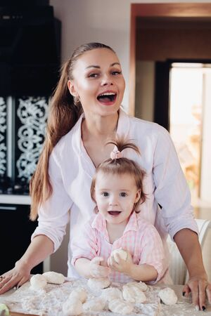 Beautiful loving mother and pretty daughter cooking together in the kitchen.