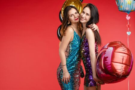 Brunette twins in black and red costumes posing at camera. Banco de Imagens