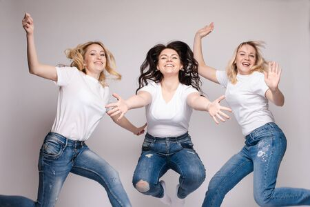Three friends in casual clothes dancing and jumping. Different, but beautiful ladies in jeans and white T-shirts getting fun and smiling. Happy young blonde and brunette women spending time together. Banco de Imagens