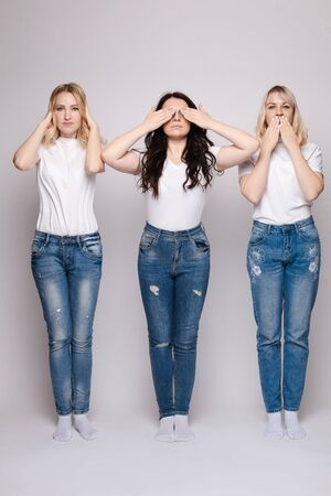 Three young women hiding different parts of their faces.