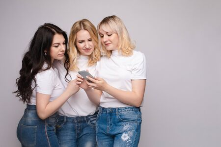 Three friends in white shirt and jeans looking at phone