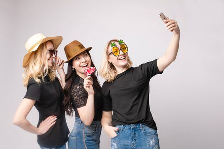 Smiling female friend wearing funny mask hat and eyeglasses posing taking selfie using smartphone
