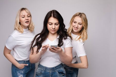 Girls looking at phone screen together.Studio portrait of two girls loking at the mobile phone while blonde girls using it. Gossip or rumour concept. Isolate. Banco de Imagens