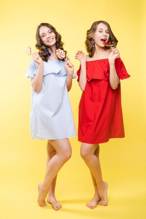 Cute brunette sisters in red and blue dresses over yellow background.