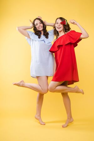 Studio portrait of gorgeous brunette sisters posing in trendy elegant dresses. Stylish outlooks. Smiling at camera. Yellow background with candy. 写真素材