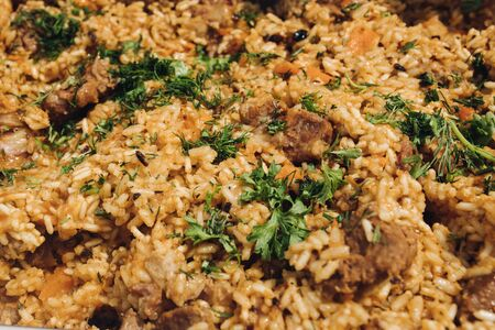 Extreme close-up fresh appetizing pilaf with meat and greenery decorating serving on plate top view Фото со стока