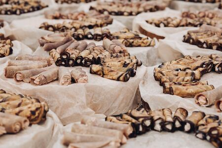Close-up of many servings of meat and vegetarian rolls made of pork and aubergine served on platters over baking paper. Special event organization. Catering concept.