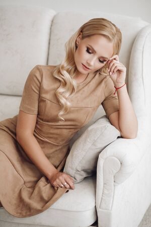 Gorgeous pretty lady sitting and holding hands on knees. Фото со стока