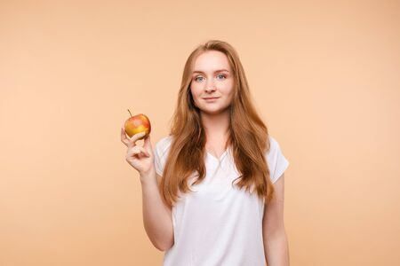 Beautiful girl with tied on back hair eating tasty apple.