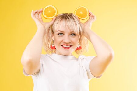 Sunny blonde keeping yellow oranges and smiling