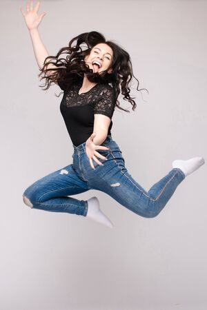 Cheerful brunette young woman in casual outlook jumping in mid air in studio.