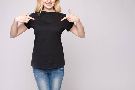 Cropped view of brunette standing in black shirt and jeans Фото со стока