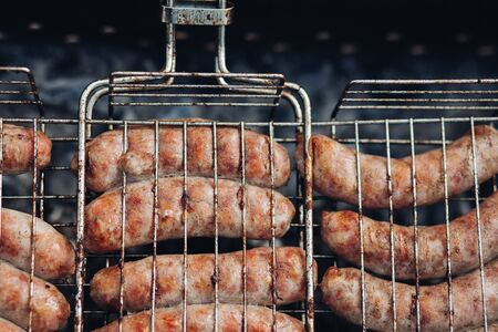 Sausages on grill at bbq party.Close-up of delicious chicken or pork sausages on BBQ. Unrecognizable cook preparing tasty sausages on grill. Stock fotó