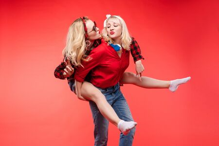 Sisters having fun giving piggyback.Stock studio portrait of two cheerful and positive trendy girlfriends or sisters having fun.