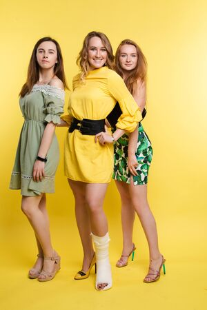 Three gorgeous ladies smiling at camera.GIrl in yellow dress with black belt posing with broken leg in plaster.