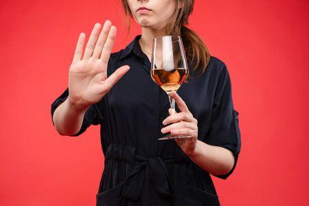 Mujer con una copa de vino gesticulando la mano con señal de stop. Aislar sobre fondo rojo.