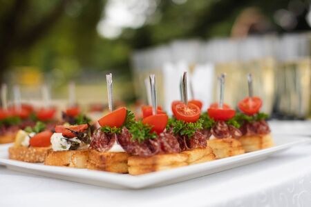 Close-up big plate with serving snack canapes fried bread tomato parsley and salami. Appetizing fresh unhealthy sandwich food decorated on table of luxury restaurant