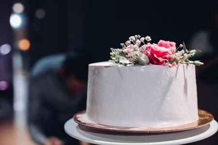 Close-up of beautiful white smooth wedding cake decorated with dried flowers on the top in artificial light.