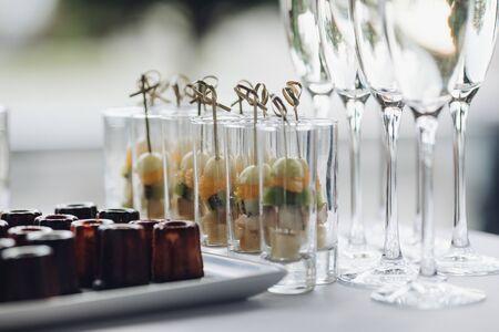 Nahaufnahme von köstlichen gesunden Vorspeisen, die auf der Geburtstagsfeier serviert werden. Selektiver Fokus von süßen Bananen, Kiwi und Orangen in Gläsern. Konzept von Catering, Desserts, Arrangement und Dekoration. Standard-Bild