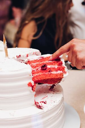 Close-up of unrecognizable person taking slice of delicious fresh red velvet cake at wedding.