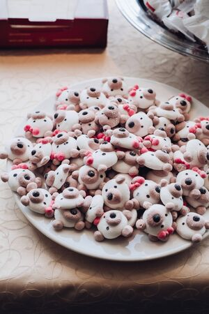 Close-up of pile of handmade marzipan biscuits in shape of bears muzzles on white plate at banquet.