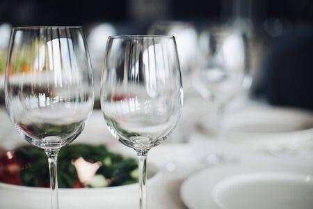 Nahaufnahme von leeren Weingläsern auf Hochzeitstisch im Fokus.