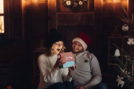Happy couple under snowfall looking at magical present.