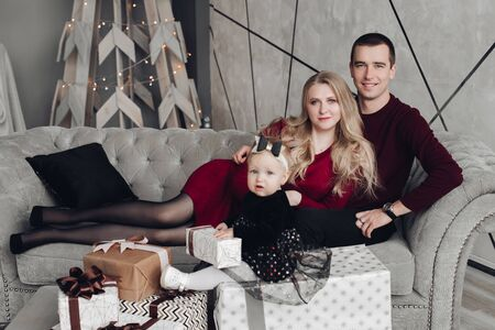 Cheerful and jovial family with baby on gray sofa. Imagens