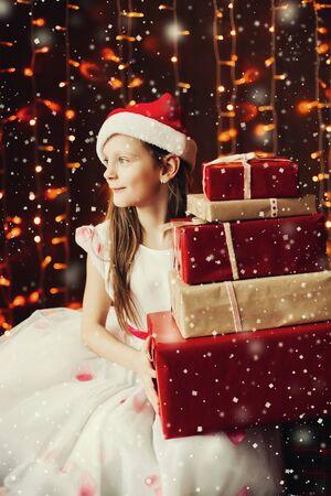 Pretty girl in santa s hat preparing presents for family to Christmas.