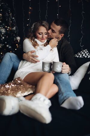 Romantic couple with mugs on bed.New Year