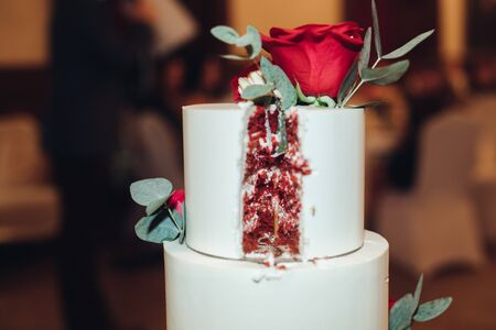 Close-up tasty big appetizing fresh piece of layered biscuit cake covered by whipped cream icing. red velvet