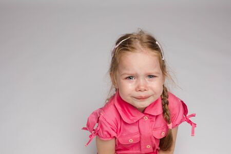Little girl in pink shirt crying on isolated background