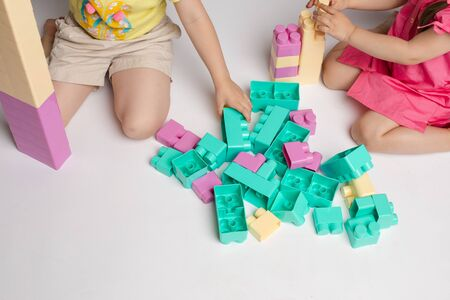 Two enthusiastic little girl playing assemble constructor full shot at studio white background