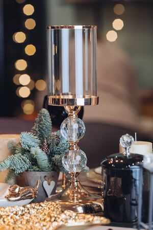 Close up of high glass candlestick on table near Christmas decoration. New Year eve concept