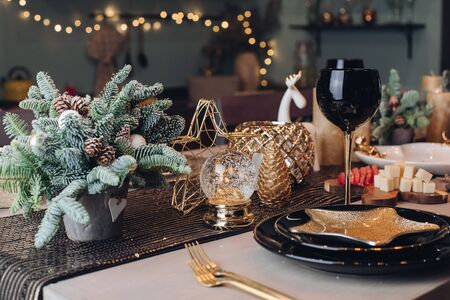Thanksgiving table setting among white candles and cones