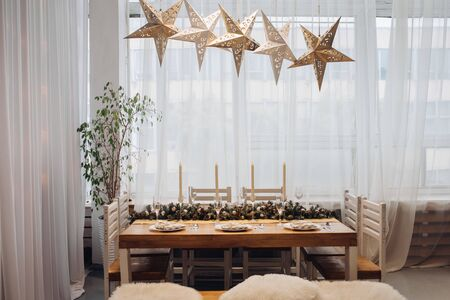 View over beautifully decorated dining table for six people with fir branch with pine cones in the middle of the table, served flutes and plates. Five decorative lamps in shape of stars over the table. Christmas dinner concept.