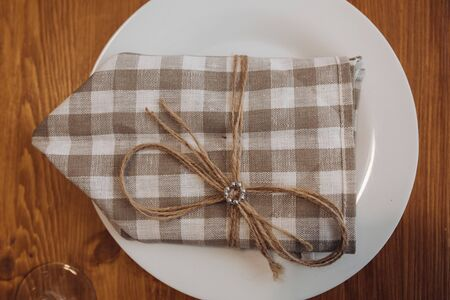 Close-up of checked napkin on white plate.