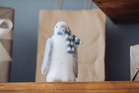 Close-up of light blue toy penguin on brown wooden shelf.