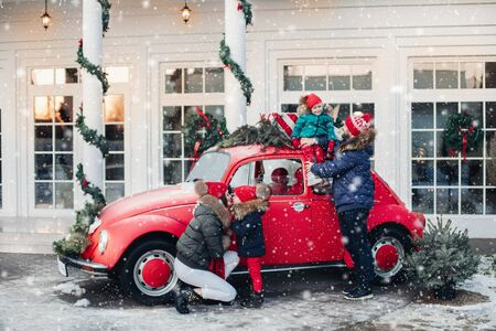 Parents and children with New Year presents and Christmas tree. Dad, mom, daughters and son are going for Christmas holidays by car