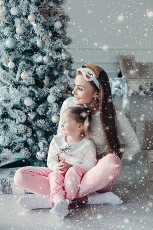 Happy festive mother and daughter hugging sitting together at decorating beautiful Christmas tree