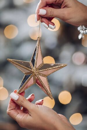 Close up of woman with toy glass decorative star in hands. New Year eve concept