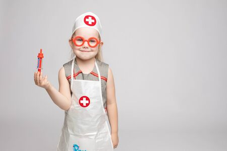 Little cute funny girl playing wearing doctor uniform holding toy syringe looking at camera