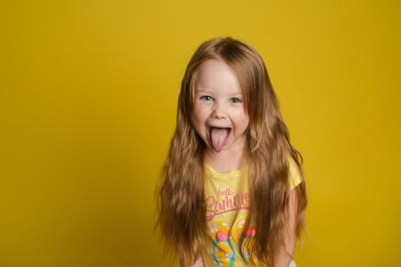 Portrait of beautiful little girl with long hair smiling posing isolated at yellow studio background