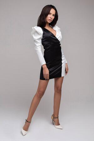 Stylish fashion girl posing in white and black dress looking at camera medium shot. Stok Fotoğraf