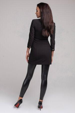 Stunning slim model in bright black dress and black heels.