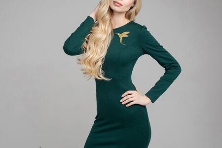 Cropped stock photo of anonymous blonde model with long hair wearing beautiful sking-tight dress of deep green color with golden hummingbird brooch on chest. Holding arms on her hip. Cutout on white or grey. Stok Fotoğraf