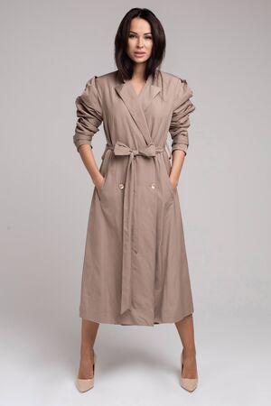 Pretty young lady in elegant trench coat walking in studio