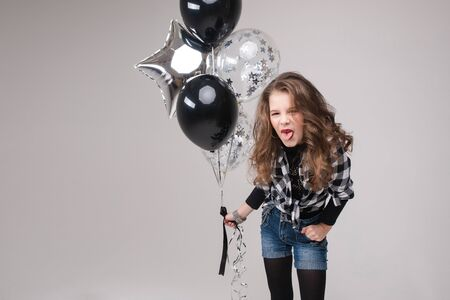 Cool pre-teen girl with rock sign. She is showing rock n roll or horn sign, gesturing at camera and pouting her lips with two air balloons. Stock studio portrait isolate on grey.