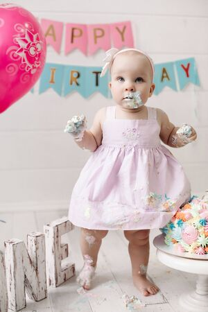 Cute little baby girl wearing pink dress get dirty in cake cream celebrating holiday